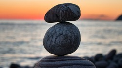 Fun holiday at sea, beach activities. The pyramid (cone) is built of round stones (small boulders) in balance (equilibrium), against sunset. Variegated and striped stones of different shapes