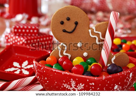 Fun image of smiling gingerbread man with peppermint stick in holiday snowflake dish with colorful candy.  Wrapped gifts and candies in soft focus in background.    Macro with shallow dof. #109984232