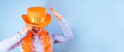 Fun in King's Day in Holland, traditional festival on April 27 in the Netherlands. Little girl in a festive orange hat on a blue background eats colored donuts. Copy space