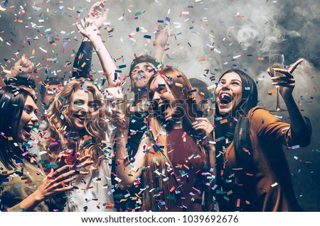 Fun in motion. Group of beautiful young people throwing colorful confetti while dancing and looking happy