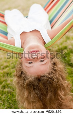 Fun in the garden - lovely girl playing in colorful hammock