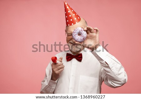 Fun, joy, celebration and holiday concept. Joyful positive mature retired male wearing red cone hat, bow tie, white shirt and spectacles relaxing at birthday party, holding doughnut and whistle #1368960227
