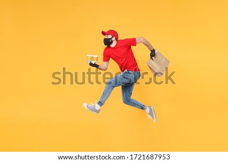 Fun jumping delivery man guy employee in red cap mask gloves hold craft paper packet food coffee isolated on yellow background studio. Service quarantine pandemic coronavirus virus 2019-ncov concept