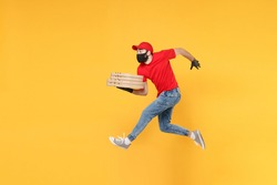 Fun jumping delivery man in red cap t-shirt uniform sterile face mask gloves isolated on yellow background studio Guy employee courier Service quarantine pandemic coronavirus virus 2019-ncov concept