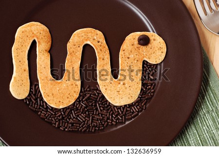 Fun kid's breakfast of a snake pancake with a chocolate chip for the eye and sprinkles added as decoration for the ground.