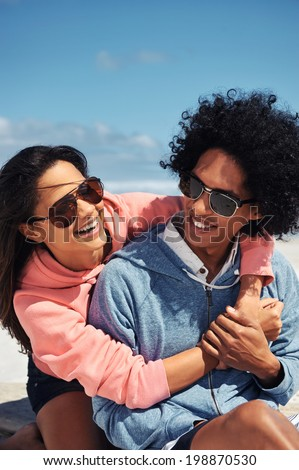 Fun Latino couple at the beach embracing and in love smiling