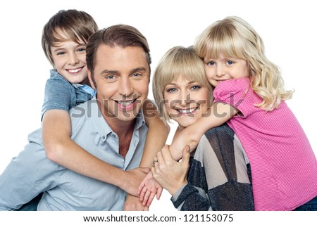 Fun loving family of four. Kids enjoying piggy ride. Indoor studio shot.