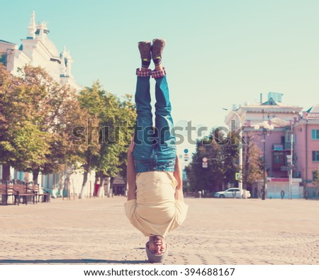 Fun man dancing. Has yellow t-shirt, blue jeans, slim sport body. Motion on great urban city. Amazing portrait. Sports acrobatic handstand. Fitness concept. Cool jump. Head over heels.