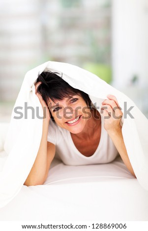 fun middle aged woman lying under duvet laughing