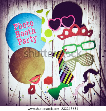Fun photo booth party background with colorful paper fashion accessories lips moustaches and balloons with text Photo Booth Party surrounded by a vignette square format