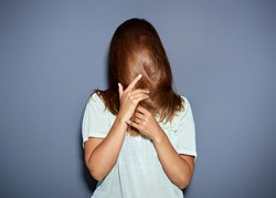 Fun portrait of a woman hiding behind her long brown hair as she pulls it down over her face with her hands, upper body over grey