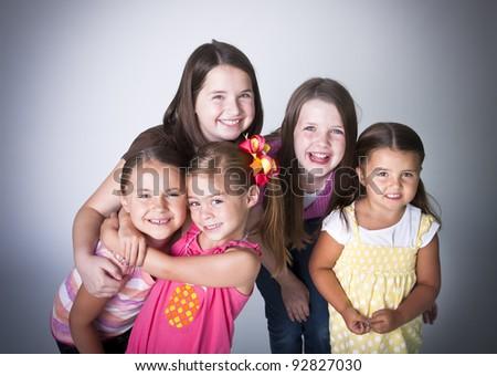 Fun portrait of five smiling happy little girls