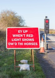 Fun road sign instructing drivers to stop when the red light shows written in a Yorkshire dialect.