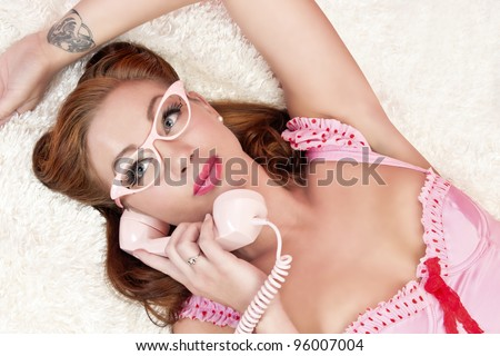 Fun, sexy pinup model wearing pink lingerie and pink glasses