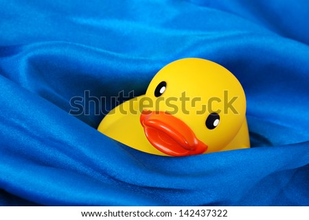 Fun still life of rubber ducky 'swimming' in waves of blue satin fabric simulating water.  Macro with shallow dof.