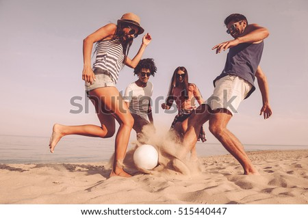 Fun time with friends. Group of cheerful young people playing with soccer ball on the beach #515440447