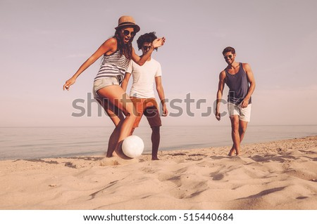 Fun time with friends. Three cheerful young people playing with soccer ball on the beach