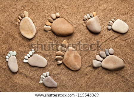 fun trace bare feet walking, made of pebble stones on the top view surface beach sand background