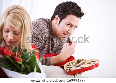 Fun Valentine\'s Day Holiday series with young Caucasian couple sitting around exchanging gifts.