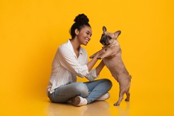 Fun With Pet. Happy Young African American Woman Playing With Her French Bulldog Puppy, Sitting On Floor Over Yellow Background In Studio, Free Space
