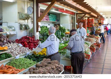 FUNCHAL, PORTUGAL - MAY 02: Unknown people visiting the vegetable market of the famous Mercado dos Lavradores on May 02, 2014 in Funchal, capital city of Madeira, Portugal