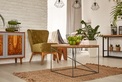 Functional flat with wooden table, dresser and green armchair