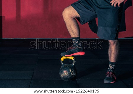 functional training with Kettle Bells Kettlebells, a young sports guy, put his foot on a kettlebell in the gym, the concept of a healthy lifestyle and functional training