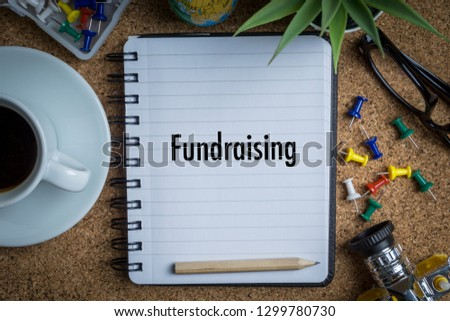 FUNDRAISING inscription written on book with globe,eyeglasses, calculator, camera, pencil and vase on wooden background with selective focus and crop fragment. Business and education concept Stock fotó ©