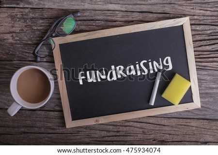 Fundraising On blackboard with cup of coffee, with glasses on wooden background #475934074