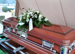 Funeral casket for a love one displayed outdoors ceremony.