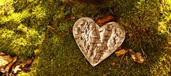 funeral Heart sympathy. panoramic image of wooden funeral heart shape in moss. Natural burial grave in the forest, woodland. Heart on grass. tree place of burial, cemetery and All Saints Day concepts