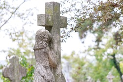 Funerary monument of a little girl crying on a cross