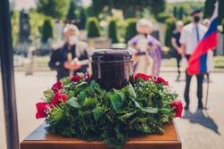 Funerary urn with ashes of dead and flowers at funeral. Burial urn decorated with flowers and chatolic christian priest in background at memorial service, sad grieving last farewell to deceased person