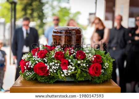 Funerary urn with ashes of dead and flowers at funeral. Burial urn decorated with flowers and people mourning in background at memorial service, sad and grieving last farewell to deceased person. Foto stock ©