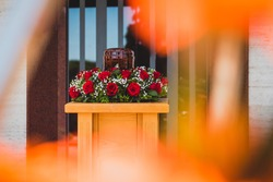 Funerary urn with ashes of dead and flowers at funeral. Burial urn decorated with flowers at memorial service on a wooden stand, sad and grieving last farewell to deceased person.