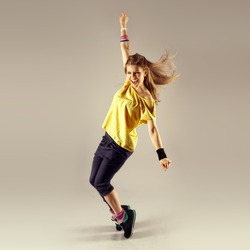 Funk dance workout. Portrait of young sporty woman in motion. Zumba