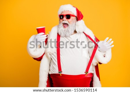 Funky big belly christmas grandfather in red x-mas hat headwear visit noel party hold disposable glass cup mug with beer feel crazy isolated over yellow color background #1536590114
