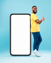 Funky black guy leaning on giant cellphone, showing thumb up gesture, recommending new mobile app or cool website, mockup for your ad design. Blue studio background
