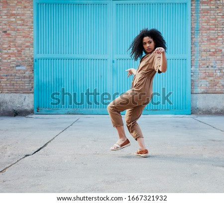 funky black woman dancing alone in the street.  Attractive African woman dancing smiling at the camera. Stockfoto ©