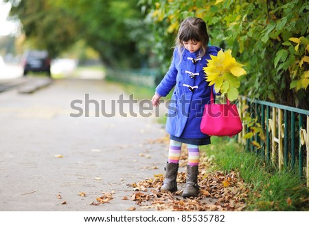 Funky little girl in blue coat walking down the street with bunch of leaves and pink bag