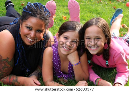 Funky pierced mother laying on the grass with her adolescent daughters smiling happily