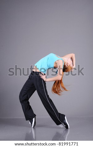funky young woman dancing isolated on grey background