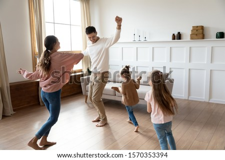 Photo of Funny active family of four young adult parents and cute small children daughters dancing together in living room interior, carefree little kids with mum dad having fun laughing enjoy leisure at home