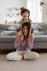 Funny active game at home: young mother give piggyback ride to laughing preschool child. Cheerful parent happy spend weekend with kid. Joyful mum and overjoyed little son together enjoy bonding time