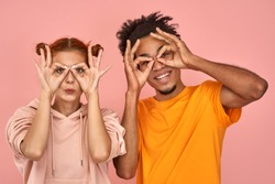 Funny african-american male and ginger caucasian female holds hands near eyes, pretends to look through binoculars tries to find love good offer, shows zero or okay gesture over eyes, on pink wall