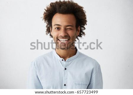Funny African man with bushy curly hair blinking his eye having warm broad smile wearing white elegant shirt posing in studio. Mixed race man elegantly dressed having fun and good mood making grimace