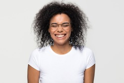 Funny african woman wearing glasses laughing at humor joke isolated on white grey studio background, happy cute black girl with afro hair having fun feeling joy enjoy laughter and positive emotions