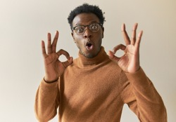 Funny amazed young dark skinned man in glasses and sweater showing ok gesture, connecting fore fingers with thumbs, saying okay, convincing you that everything is alright. Gestures, signs and symbols