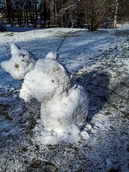 Funny and adorable melting snowman in early spring leaning to the side in sunlight, ready to fall. Changing weather and seasons