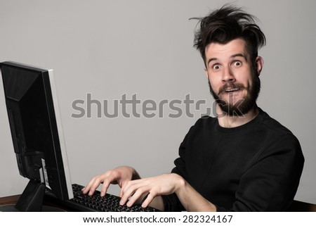 Funny and crazy man using a computer on gray background. man\'s hands on the keyboard